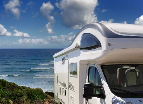 Camper parked overlooking beach and ocean