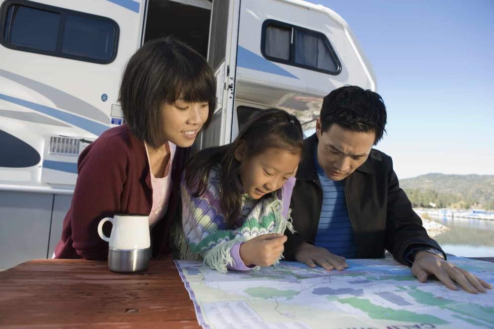Parents and daughter outside their RV, looking at a map