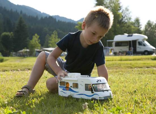 Boy playing with toy RV in front of family RV