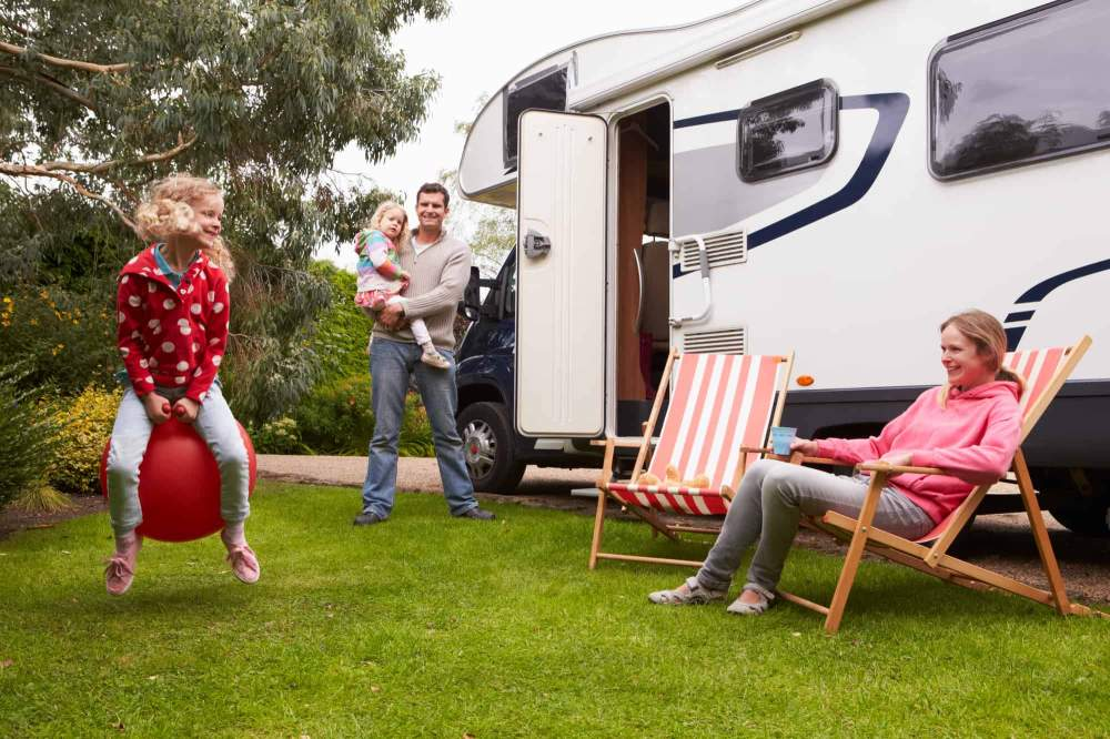 Family enjoying camping holiday with RV